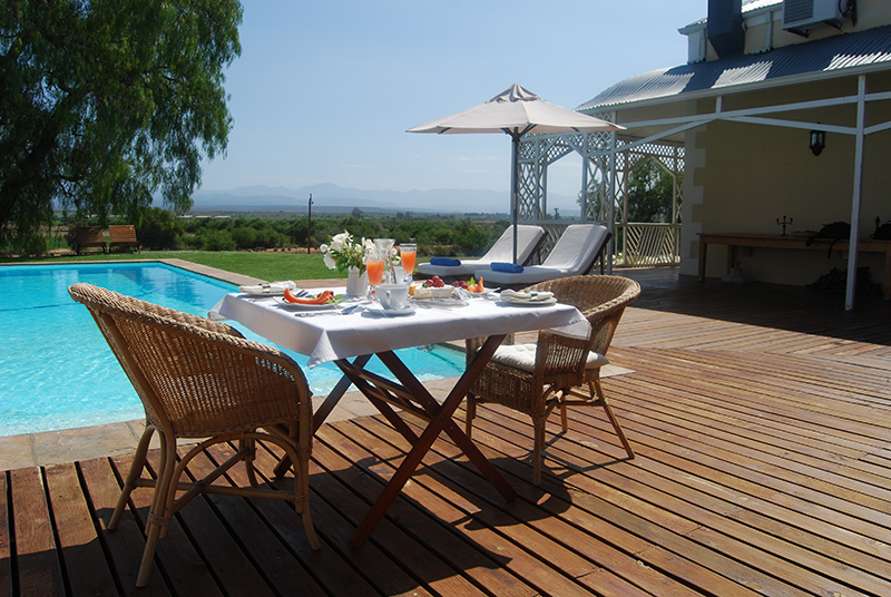 Breakfast table next to swimming pool at an Oudtshoorn Bed and Breakfast